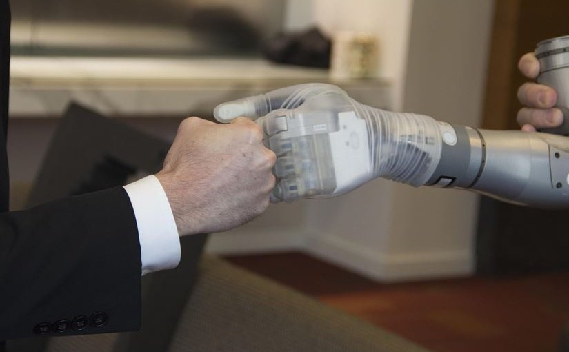 "Dr. Justin Sanchez, director of the Defense Advanced Research Projects Agency's Biological Technologies Office, fist-bumps with one of the first two advanced ""LUKE"" arms to be delivered from a new production line during a ceremony at Walter Reed National Military Medical Center in Bethesda, Md., Dec. 22, 2016 DoD photo"