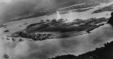Photograph taken from a Japanese plane during the torpedo attack on ships moored on both sides of Ford Island shortly after the beginning of the Pearl Harbor attack. U.S. Navy photograph, Wikipedia Commons.