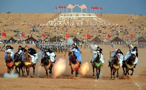 Sahrawi tribal men performing the fantasia at the Tan-Tan Moussem in Tan-Tan, Morocco. Photo by Maxim Massalitin, Wikipedia Commons.