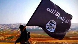 A ISIL fighter carrying the militant group's flag on Tall Dabiq which overlooks the town of Dabiq, Syria. Photo Credit: VOA, Wikipedia Commons.