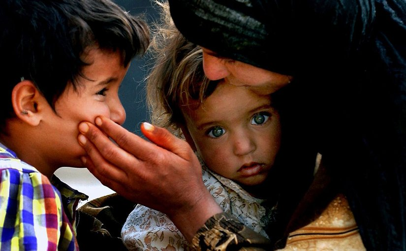 An Iraqi mother comforts her children. Photo by Russell l. Klika, SSG, DoD, Wikipedia Commons.