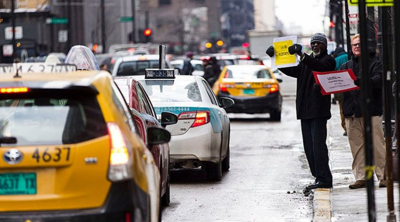 Chicago taxi drivers stand holding signs and driving around City Hall refusing to take fares in protest of the granting of a city license to ride-sharing company Uber. Photo by Scott M. Liebenson, Wikimedia Commons.