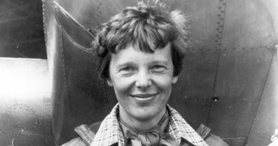 Amelia Earhart standing under nose of her Lockheed Model 10-E Electra. Photo Credit: Wikimedia Commons.