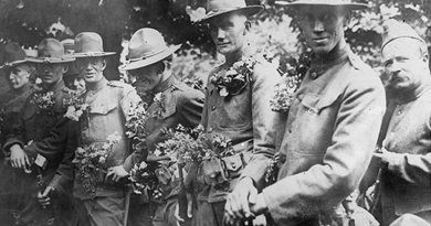 U.S. soldiers at the Picpus cemetery in Paris, where the Marquis de Lafayette is buried, are covered in flowers during a Bastille Day celebration in France, circa 1917-1920. Library of Congress photo