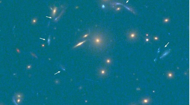 The multiple images of the discovered galaxy are indicated by white arrows (bottom right shows the scale of the image in seconds of arc). Credit Hubble Space Telescope (HST)