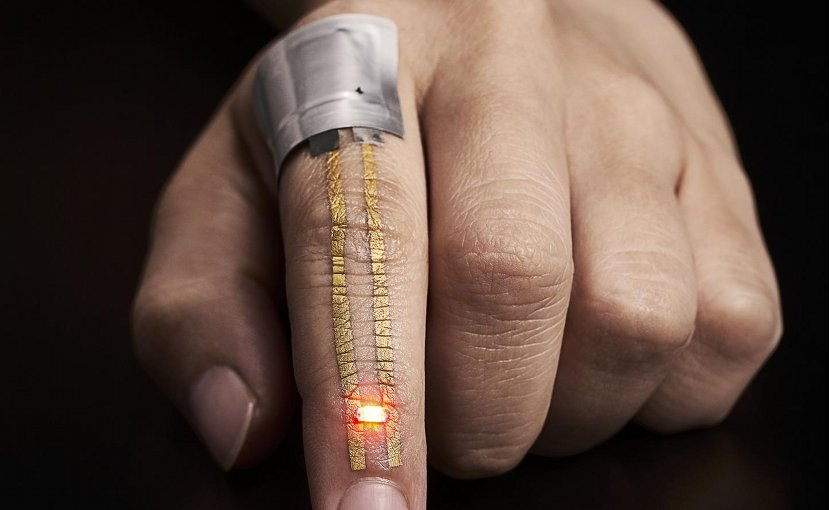 The electric current from a flexible battery placed near the knuckle flows through the conductor and powers the LED just below the fingernail. Credit 2017 Someya Laboratory.