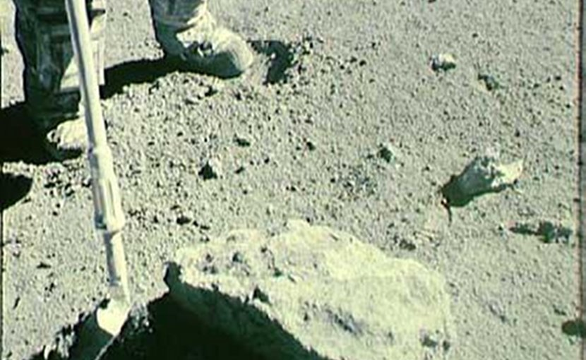 Image of the collection of the Rusty Rock, 66095, on the lunar surface by lunar module pilot, Charlie Duke and commander John Young. April 1972. Credit NASA