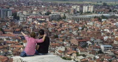 Couple sits above Prizen, Kosovo.