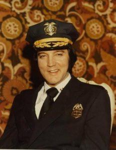 Elvis Presley posing in his Denver police uniform