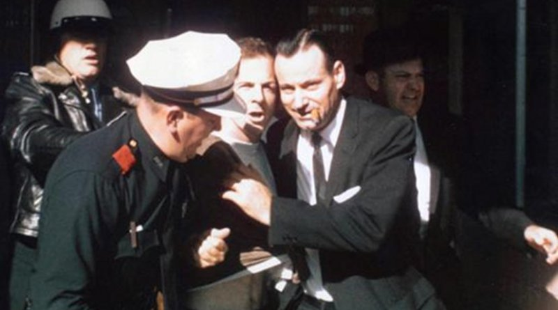 Lee Harvey Oswald being led from the Texas Theatre following his arrest. Photo by Gerald Hill, Wikipedia Commons.