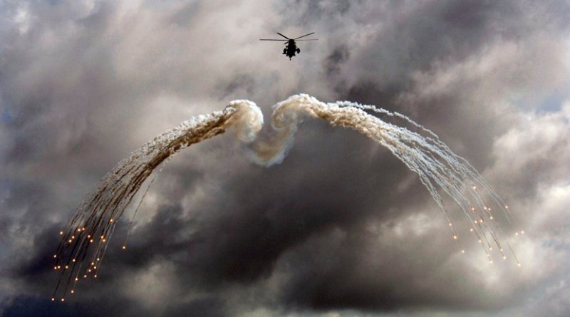 A Canadian CH 124 Sea King helicopter from HMCS Ville de Québec (VDQ) fires off defensive flares during an exercise above the Indian Ocean. Photo by MCpl Kevin Paul, Canadian Forces Combat Camera.