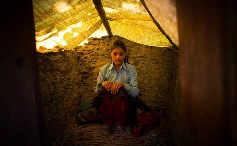 Wearing her school uniform, Jaukala, 14, poses for a photo in the family's chaupadi shelter, a squat shed measuring approximately 1 meter by 2 meters, in Rima village, Achham, Nepal. A tarp serves as a temporary roof to this structure, still under construction. Jaukala must sleep here while she has her period. Courtesy of Allison Shelley