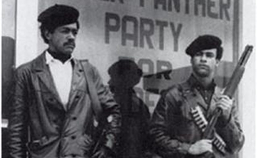 Black Panther members Huey Newton and Bobby Seale standing in streets, armed with shotguns. Source: Wikipedia Commons.