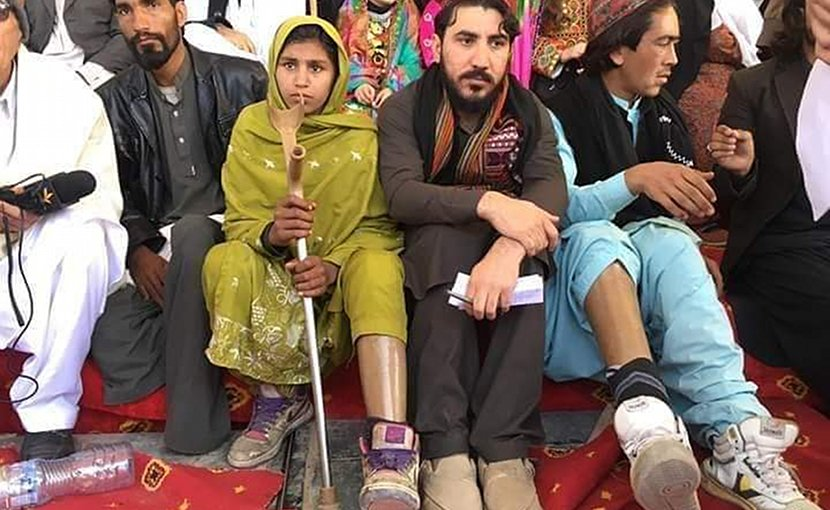 Manzoor Pashteen (center) sitting with landmine victims in Tank, Khyber Pakhtunkhwa, Pakistan, at a PTM gathering on the first anniversary of the murder of Naqeebullah Mehsud. Photo Credit: Khestwol, Wikipedia Commons.
