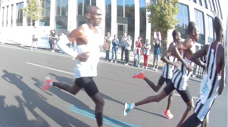 Eliud Kipchoge (left) and his three pacemakers (right) about 30 minutes into the run, during the Marathon world record in the 2018 Berlin Marathon. He is shown a few seconds before crossing the river Spree. Photo Credit: C.Suthorn, Wikipedia Commons