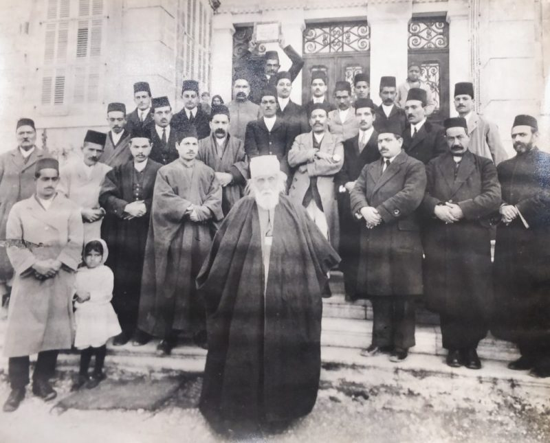 Guardian  of the Faith, Abdul Baha (centre), surrounded by Indian and local  Baha'is on the steps of his home in Bahji, near Haifa.