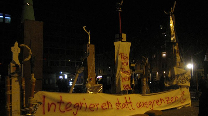 """On the evening of the vote, demonstrations against the result were held in Switzerland's major cities. The banner beneath the makeshift minarets reads: """"Integrate rather than exclude."""" Photo Credit: MCaviglia, Wikipedia Commons"""
