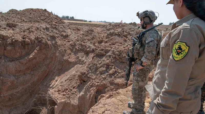 A member of the U.S.-led coalition and a member of a local security force observe the destruction of a former fortification in northern Syria. Photo Credit: Army Staff Sgt. Andrew Goedl
