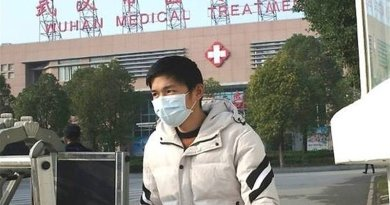 Man wearing mask in front of a hospital in Wuhan, China. Photo Credit: Tasnim News Agency