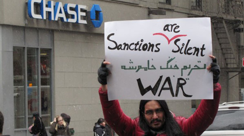 "Protester's sign decries sanctions, ""a silent war"". Photo credit: Campaign for Peace and Democracy, 2013"