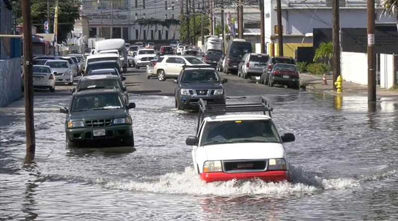Vehicles drive through a flooded road in Honolulu. CREDIT Hawaii Sea Grant King Tides Project