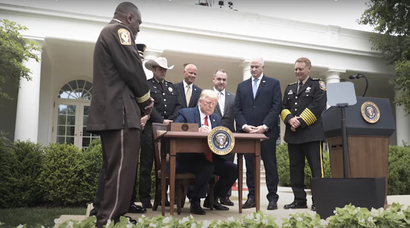 US President Donald Trump signs an executive order outlining some police reforms. Photo Credit: White House video screenshot