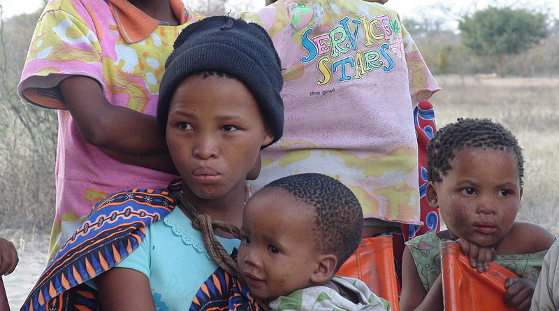 The daughters of a small community of San bushmen living in Namibia. The baby boy is the girl's brother. Photo Credit: Nicolas M. Perrault, Wikipedia Commons