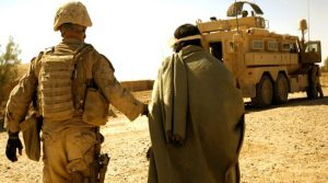Marine with Combined Anti-Armor Team 1, 1st Battalion, 5th Marine Regiment, escort enemy prisoner of war away for questioning after discovering illegal drugs and improvised explosive device–making material, Helmand Province, Afghanistan, October 19, 2009 (U.S. Marine Corps/John McCall)