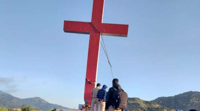 Police remove a cross from a hill near a Catholic parish in Karnataka state on Sept. 23 after accusing Christians of erecting it without permission on government land. (Photo supplied)
