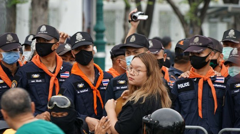Protest leader Panusaya Sithijirawattankul stands in front of a police barrier as she holds a letter addressed to Thailand's king asking him to support political reforms, Sept. 20, 2020. Photo Credit: Nontarat Phaicharoen/BenarNews