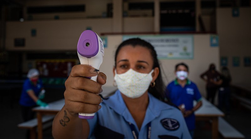An employee at the State Full-Time School Professor Jacimar da Silva Gama, located in the south of Manaus, Amazonas, Brazil, is seen taking the temperature of students arriving for class on September 14, 2020. Photo: IMF / Raphael Alves, (CC BY-NC-ND 2.0).