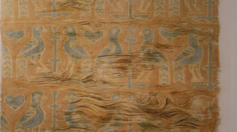 The motive is birds, probably peacocks, flanking a stylized tree or cross. It consists of several silk pieces sewn together. One piece, 30x40 cm, covers the front of the pillow and about a third of the back, while the rest consists of strips about 5 cm wide, cut off without regard to the pattern. The colors are golden and two light blue shades. CREDIT: © Nationalmuseet / The National Museum of Denmark