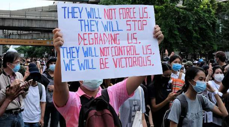 A young Thai protester holds up a sign at a mass rally against the military-led government at a key intersection in Bangkok's commercial heart on Oct. 15. (Photo: UCA News)