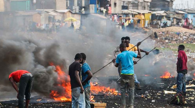 Youths engaging in open burning of waste at a dump. A report says this potentially releases long-term environmental pollutants and toxic substances linked to immunological and developmental impairments. Copyright: Fairphone, (CC BY-NC 2.0). This image has been cropped.