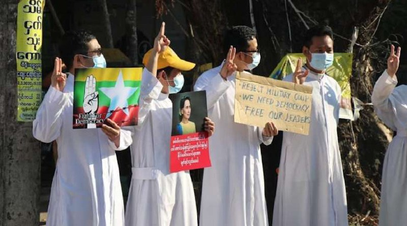 Catholic priests hold a picture of State Counselor Aung San Suu Kyi while others display the three-finger salute during an anti-coup protest in Pathein, Irrawaddy division, on Feb. 10. (Photo: OSC Pathein)