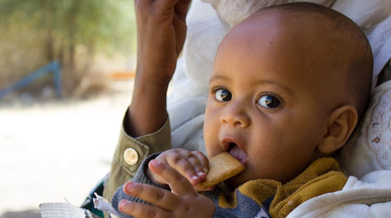 A seven-month-old baby displaced with his mother due to conflict in Tigray eats a high energy biscuit to boost his nutrition levels. Credit: UNICEF/Esiey Leul Kinfu