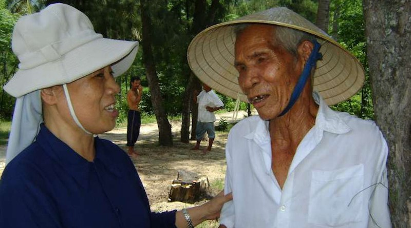 Sister Mary Nguyen Thi Loi talks with Dang Van Loc outside his house in Binh Dinh province on March 2. (Photo: UCA News)