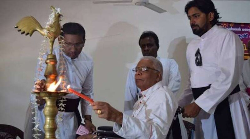 Bishop Rayappu Joseph lights an oil lamp during the launch in 2016 of 'A Living Hero', a book about his life. (Photo: UCA News reporter)
