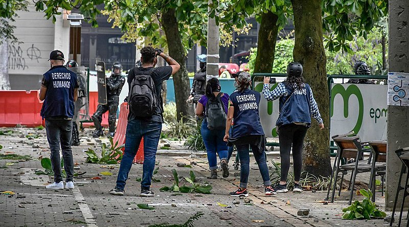 Members of Defensores de Derechos Humanos (DDHH) try to hold talks with Colombian ESMAD police during protests. Photo Credit: Humano Salvaje, Wikipedia Commons