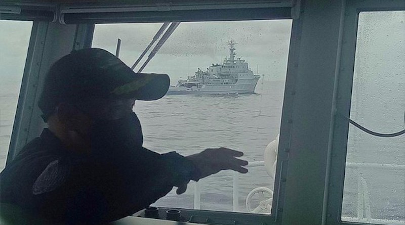 A Philippine Coast Guard officer aboard the BRP Cabra observes a Chinese Navy warship near the Marie Louise Bank in the South China Sea, July 13, 2021. Courtesy Philippine Coast Guard