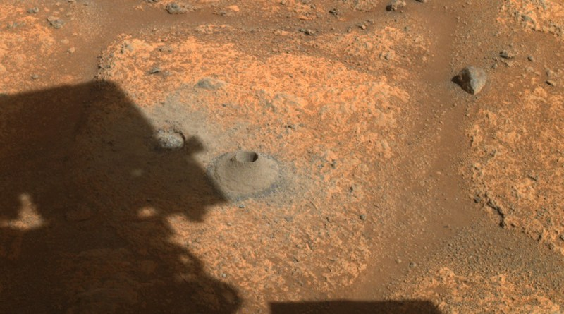 """This image taken by one the hazard cameras aboard NASA's Perseverance rover on Aug. 6, 2021, shows the hole drilled in what the rover's science team calls a """"paver rock"""" in preparation for the mission's first attempt to collect a sample from Mars. Credits: NASA/JPL-Caltech"""