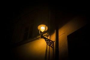 Lampadaire allumé dans une rue sombre