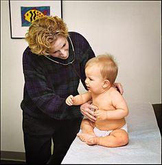 Photographie d'une pédiatre auscultant un bébé