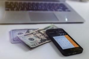 photographie d'un laptop, smartphone et billets