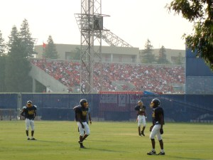 Fans pack Beiden Field to welcome home the Fresno State Bulldogs baseball team after their fairytale College World Series triumph. In the foreground, the next generation of football players try to concentrate on their training session - perhaps dreaming of one day emulating the achievement of their sporting brothers.
