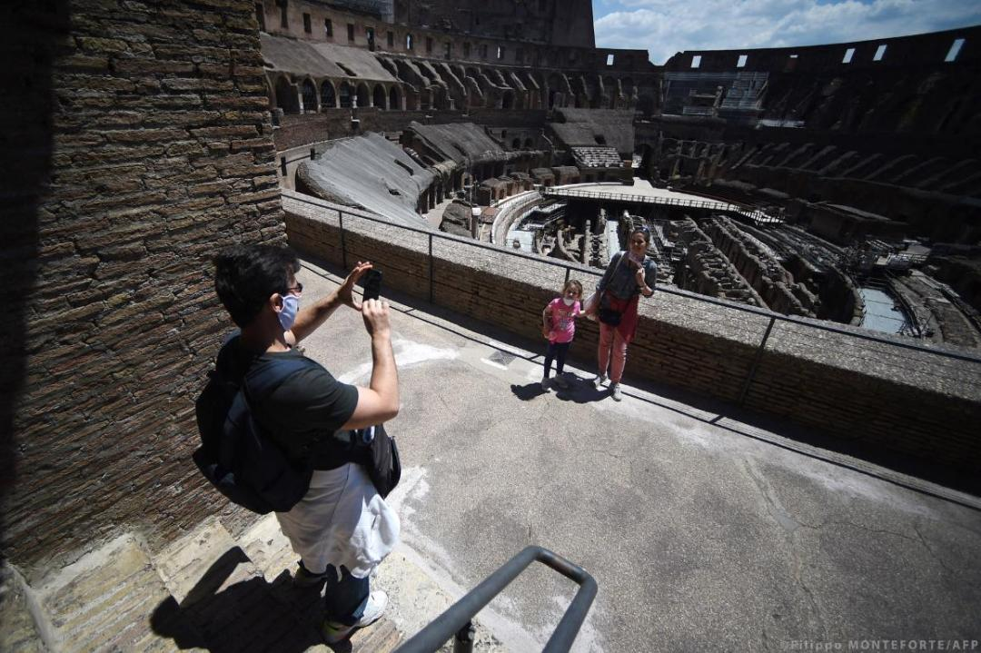 Visitors pose for a photo at the Colosseum monument which reopens to the public on June 1, 2020 in Rome. ©AFP/Filippo MONTEFORTE