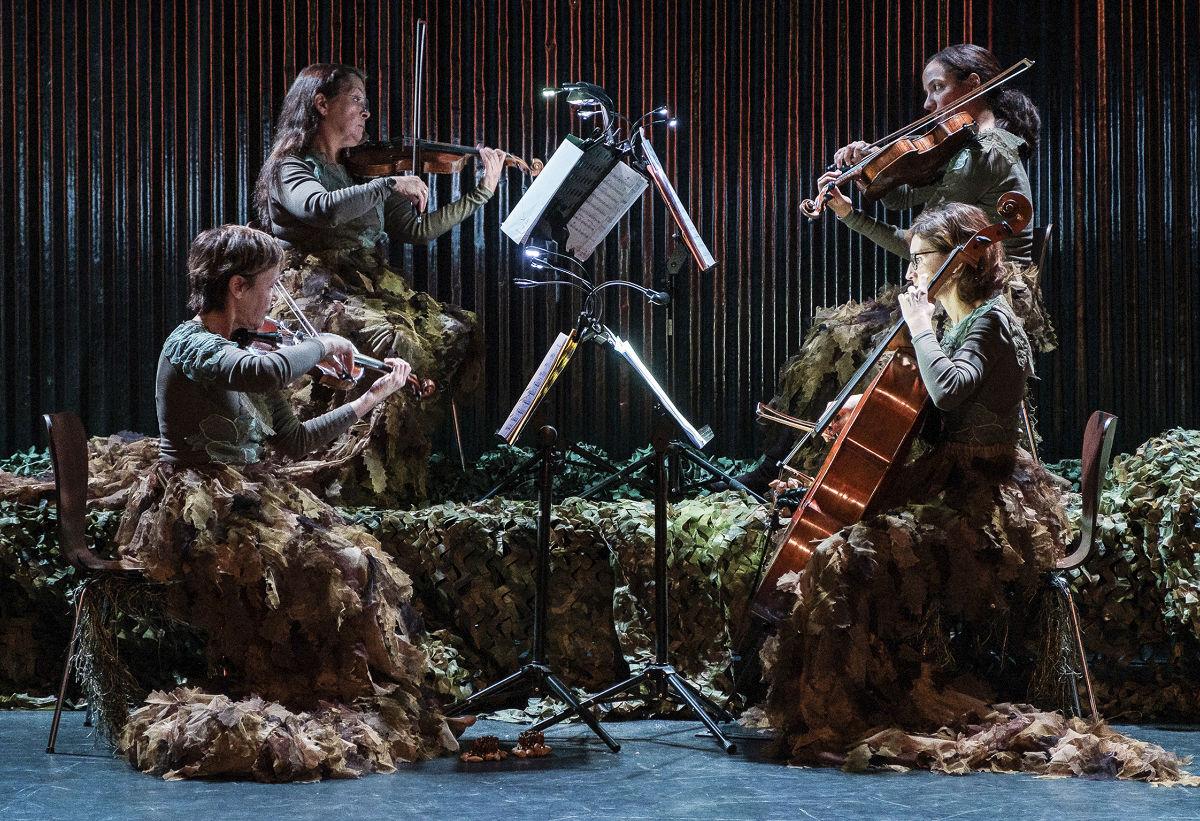 Vier Frauen sitzen mit langen Tarnröcken auf einem kleinen Podest und spielen ein Streichquartett