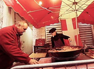 Market seller with a pan of Diot au Vin Blanc at the Fete du caion in Annecy France 2014