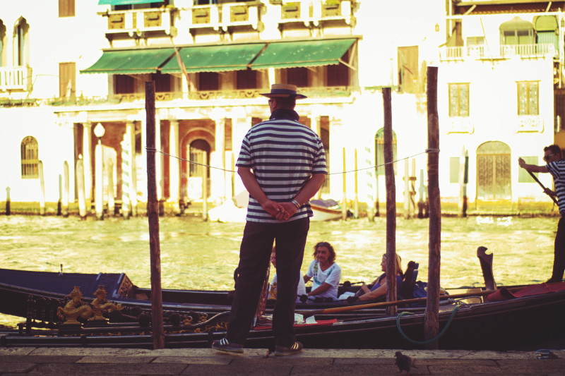 A lone gondolier on a canal bank in Venice