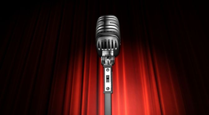 A microphone in front of a red curtain